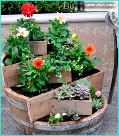 A flower bed of wooden barrels