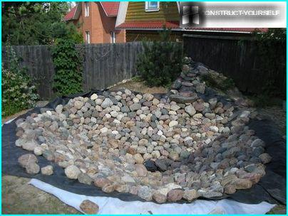 Decorating the bottom of the pond, lined agrovoloknom, river stones