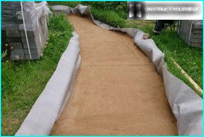 Aizbērtas smiltis uz dārza celiņa