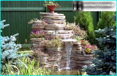 A decorative waterfall in the corner of the garden